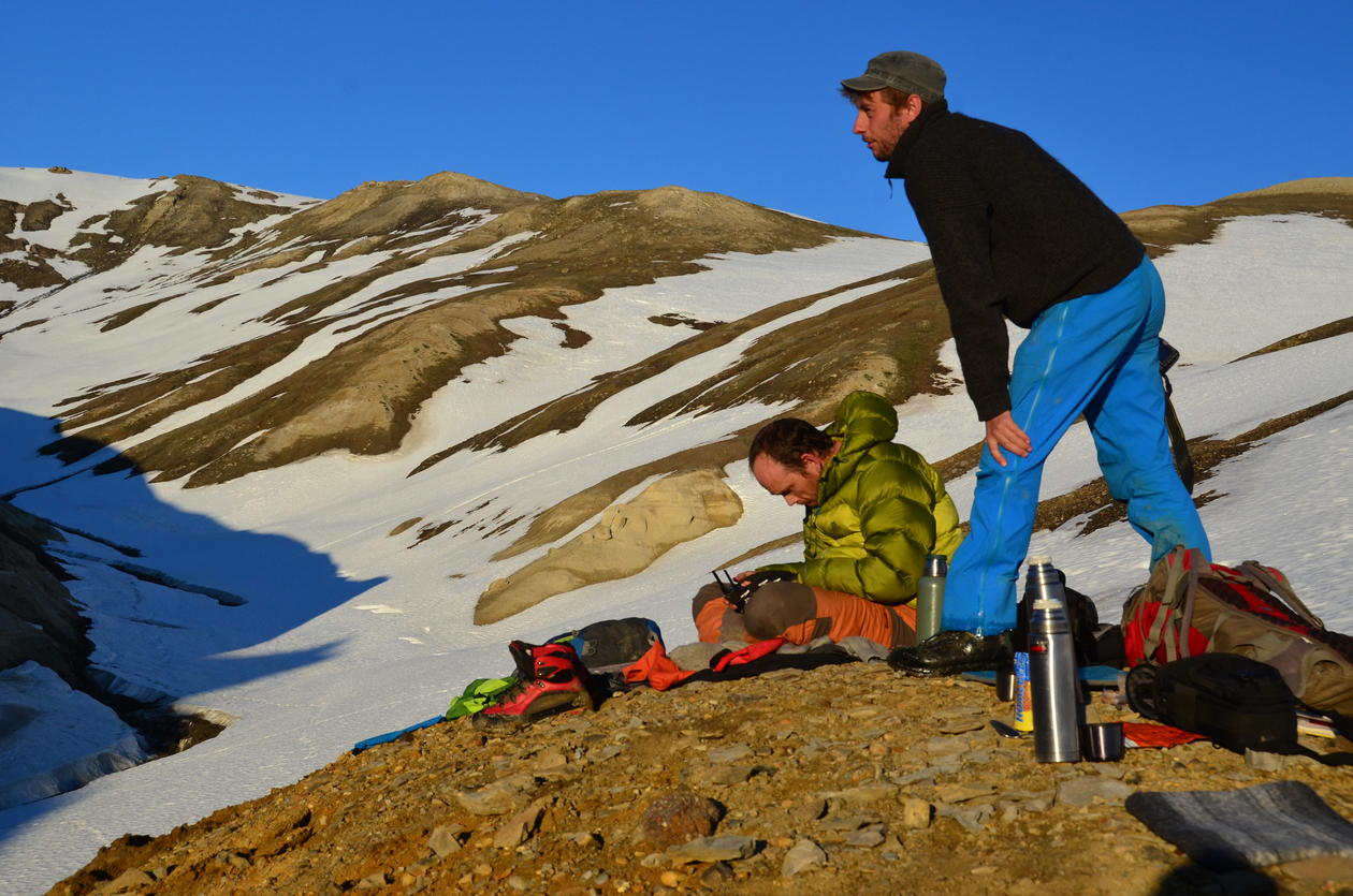The whole team tramping through a snow packed valley towards a promising outcrop.