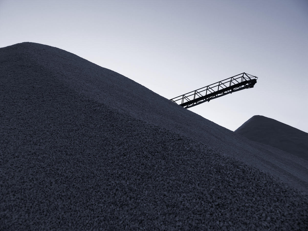 Belt conveyor and loads of coal at the harbor quay
