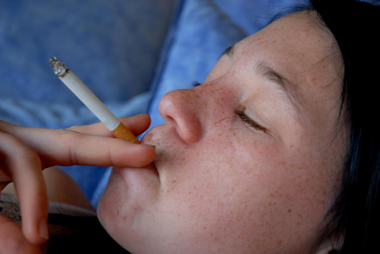 ungdom som røyker - hen ligger på en pute med øynene lukket og har en sigarett mellom fingrene