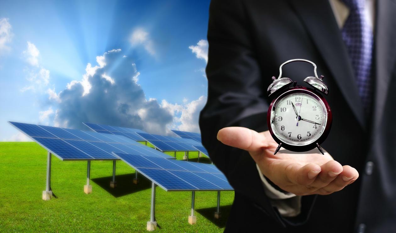 Solcellepaneler og en mann med en klokke