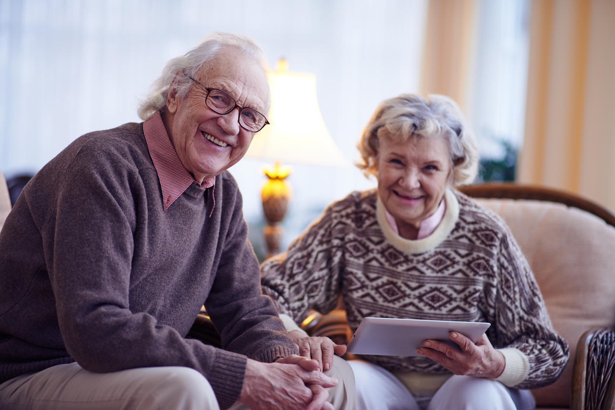 Two elderly people looking at an Ipad