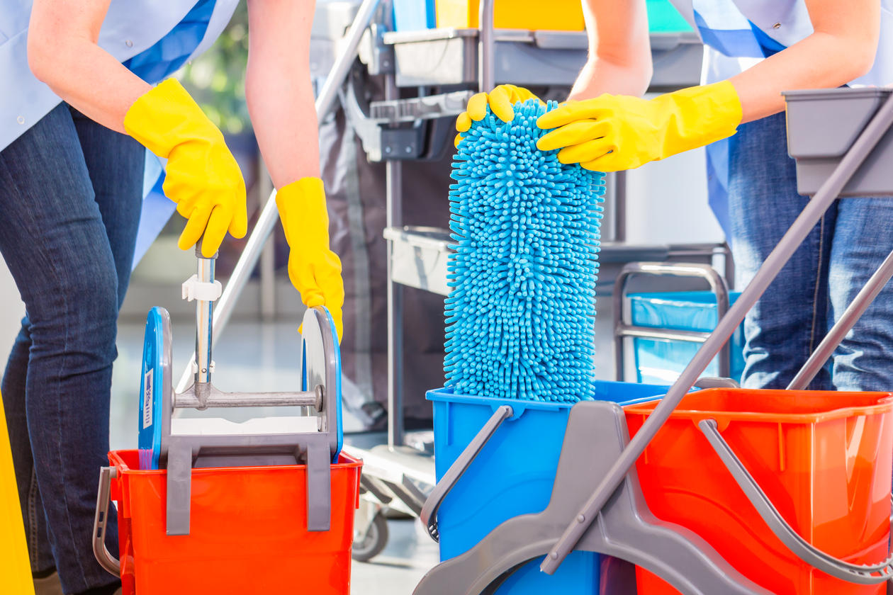 Showing cleaners at work, preparing to clean floors, used to accompany article about how many cleaners suffer bad health unless preventive measures are taken.