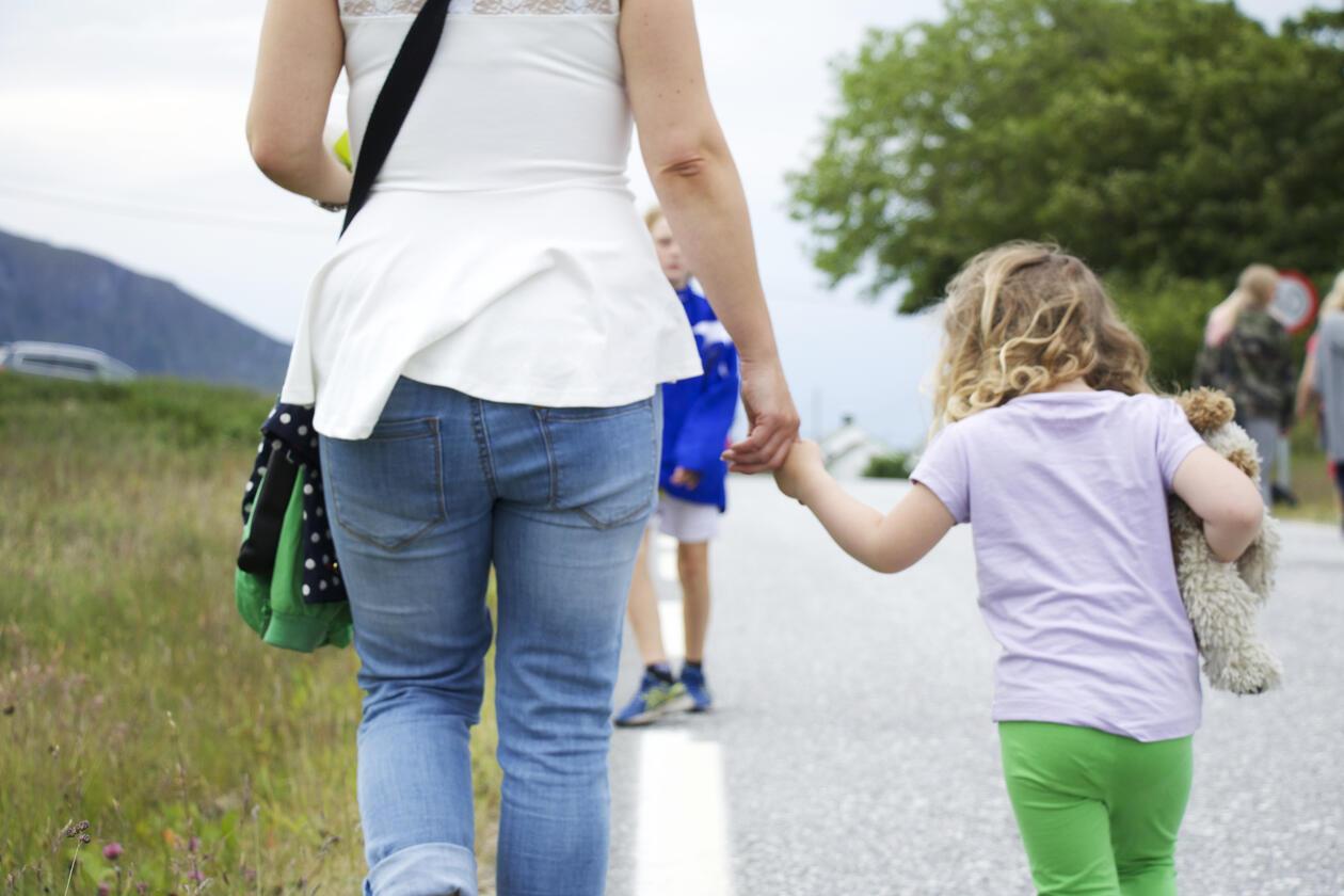 Kvinne og et lite barn går hånd i hånd bortover en vei. Barenet er ca 5 år gammelt og holder en bamse. Du ser dem bakfra, i bakgrunnen skimtes en gutt en fotballustyr, det er sommer, og blomster på engen og trærne er grønne