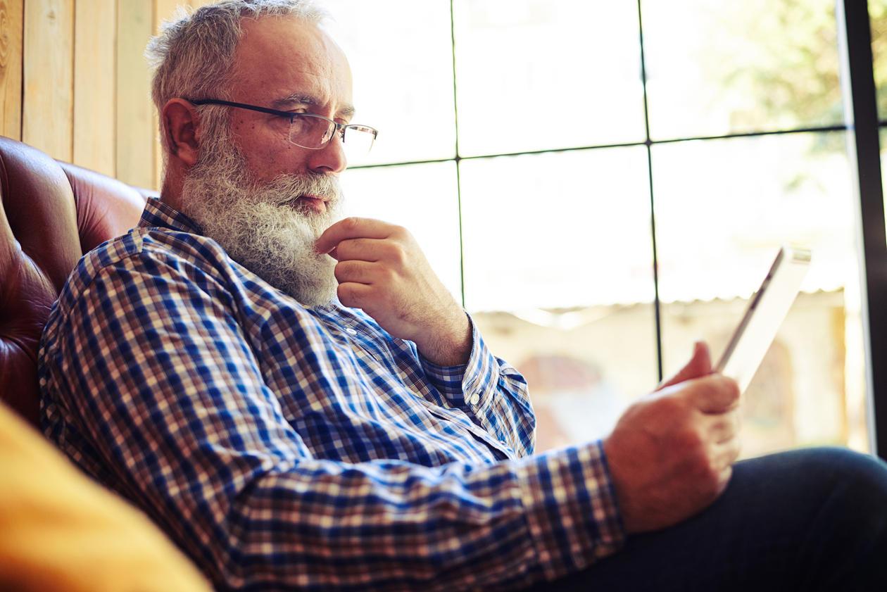 Eldre mann leser på mobil