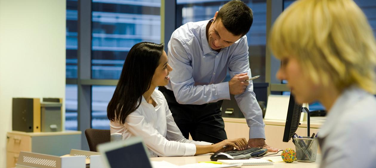 Mann snakker med kvinne som sitter ved kontorpult