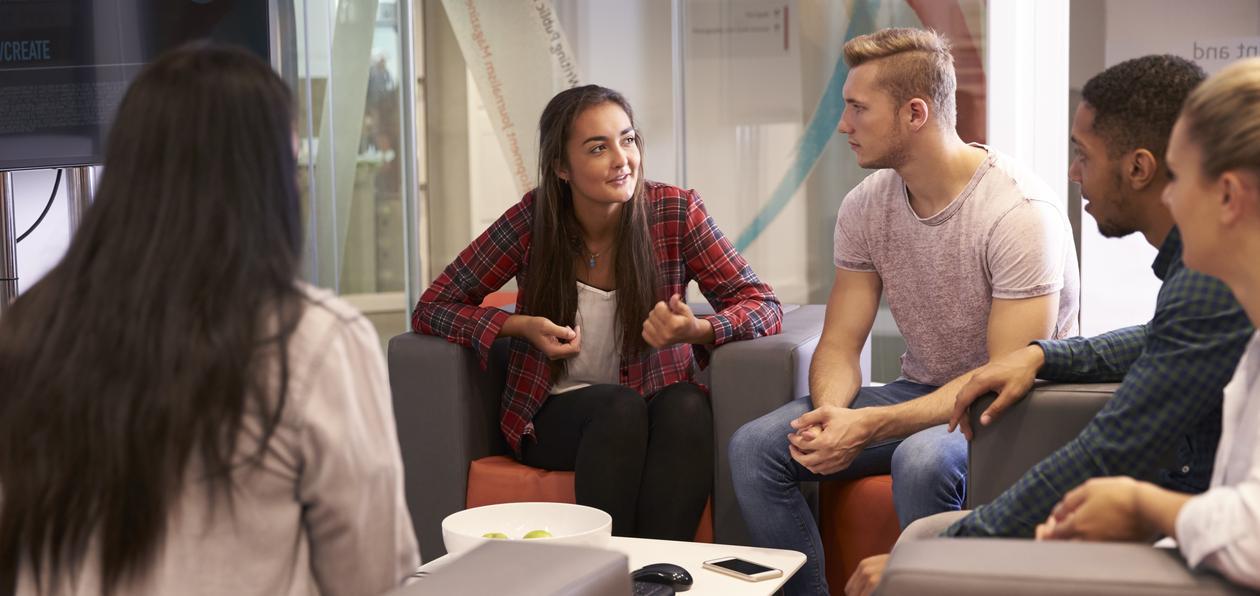 Fem studenter diskuterer sittende i en sofa