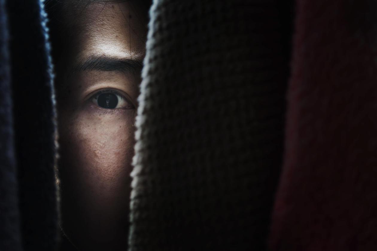 Woman hiding behind curtan
