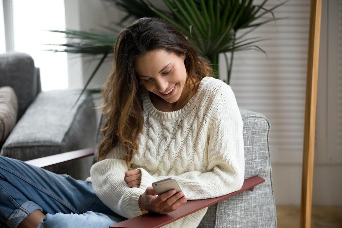 Kvinne sitter i sofaen og ser på mobilen