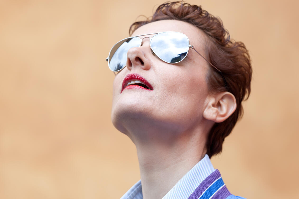 Woman with sunglasses looking up in the sky