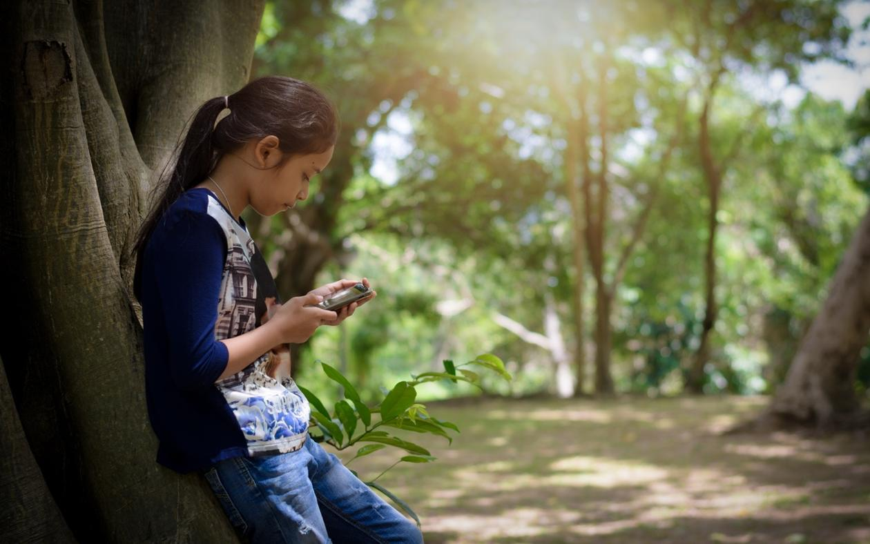 Girl leaning against a tree, looking at her phone.