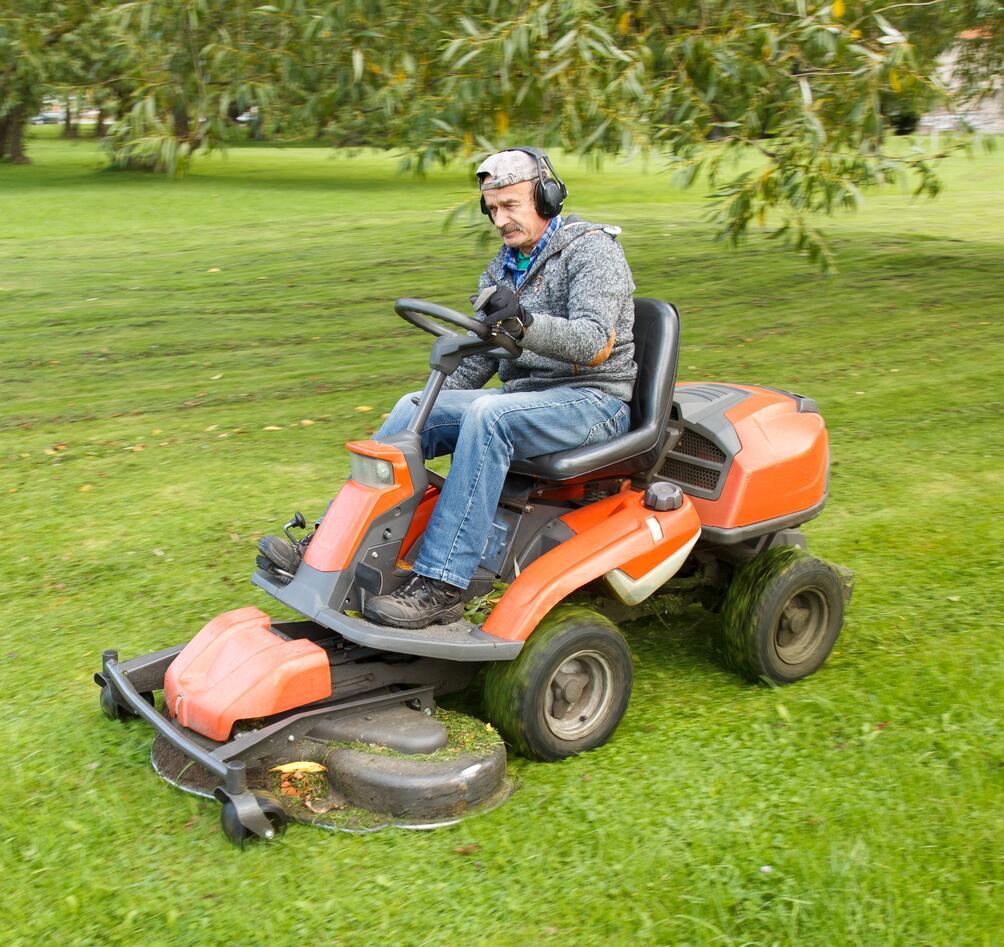 Man driving a lawn mower.