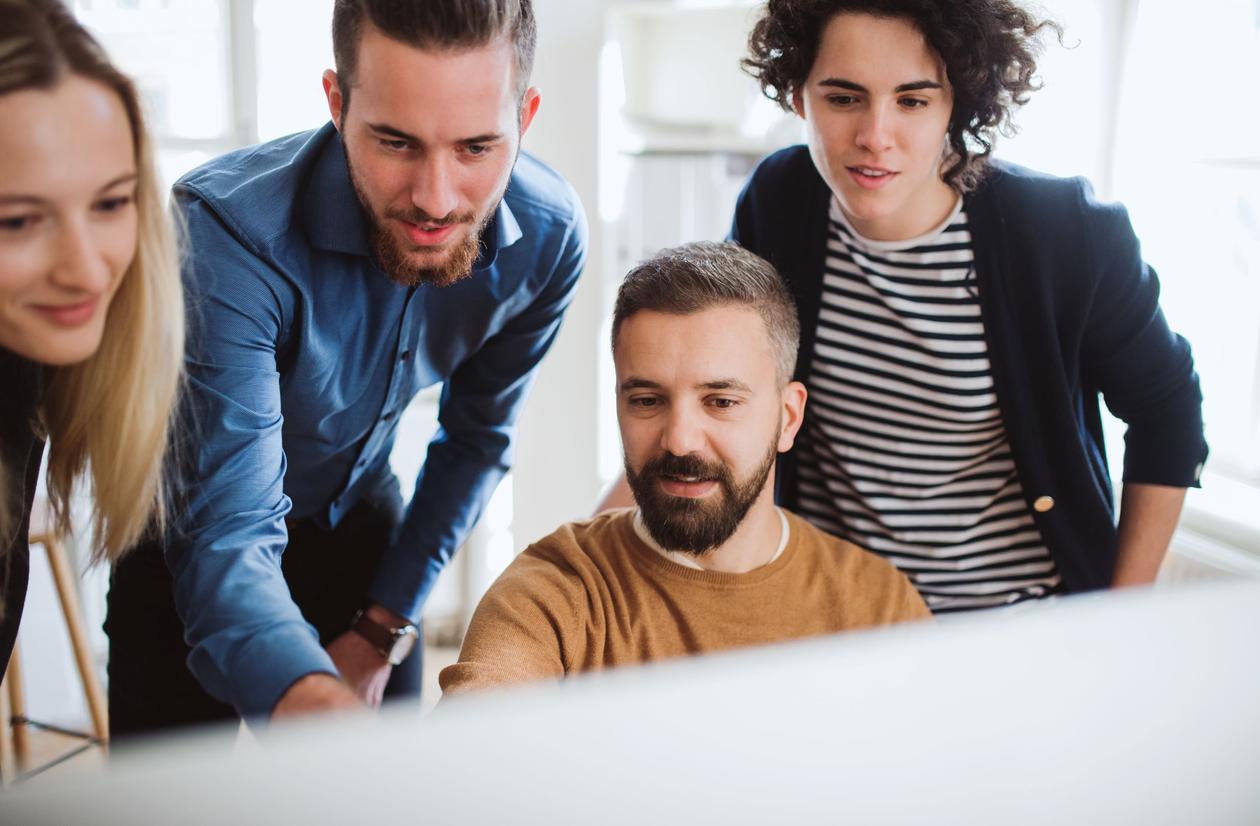 Bildet vise mennesker som arbeider foran en pc-skjerm