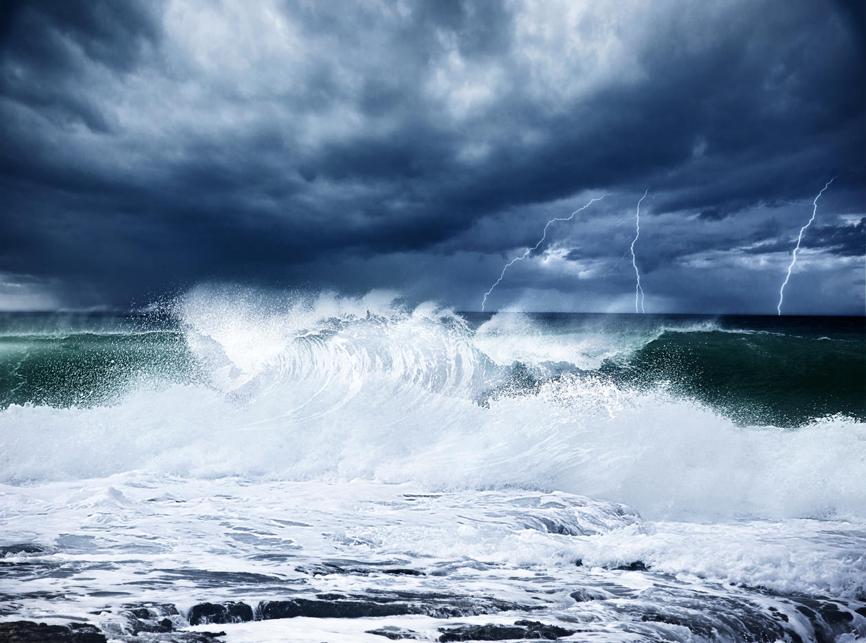 Illustration photo showing a stormy ocean with lightning in a dark blue sky.