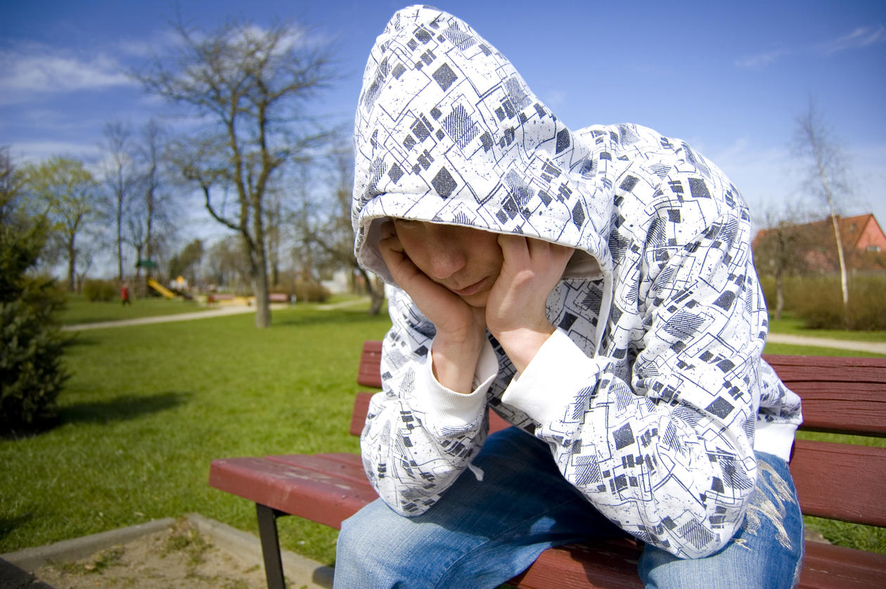 En ung gutt sitter på en benk med hodet hvilende i hendene.