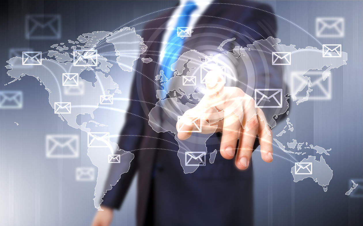 Upper body of man in suit and tie pointing towards a screen which shows a world map and small envelopes, indicating use of social media.