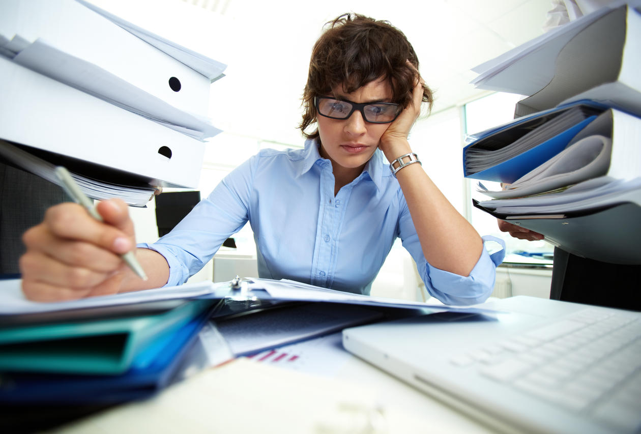 Extremely overworked woman at her desk surrounded by paper work; used to illustrate article about research on work addiction.