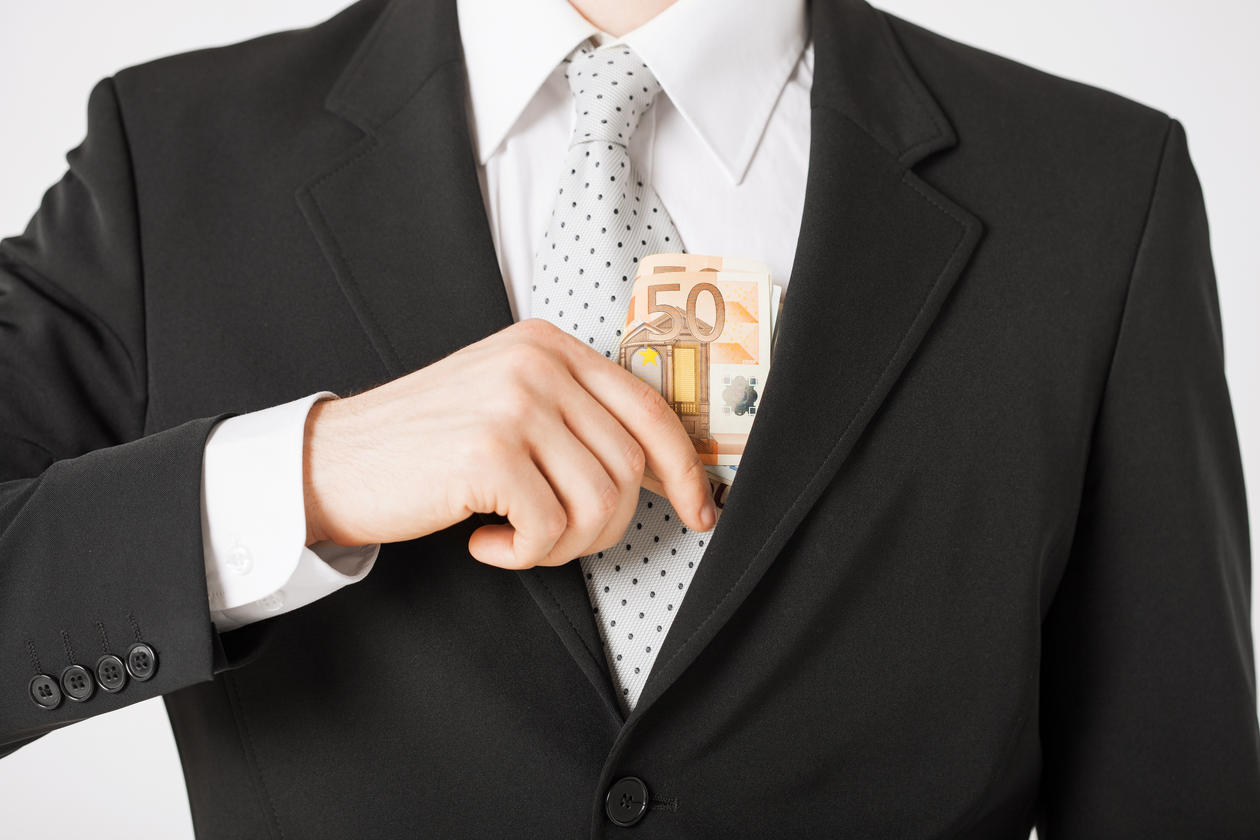 Illustration photo of man in suit and tie putting money in his inner breast pocket. Used to illustrate article on corruption.