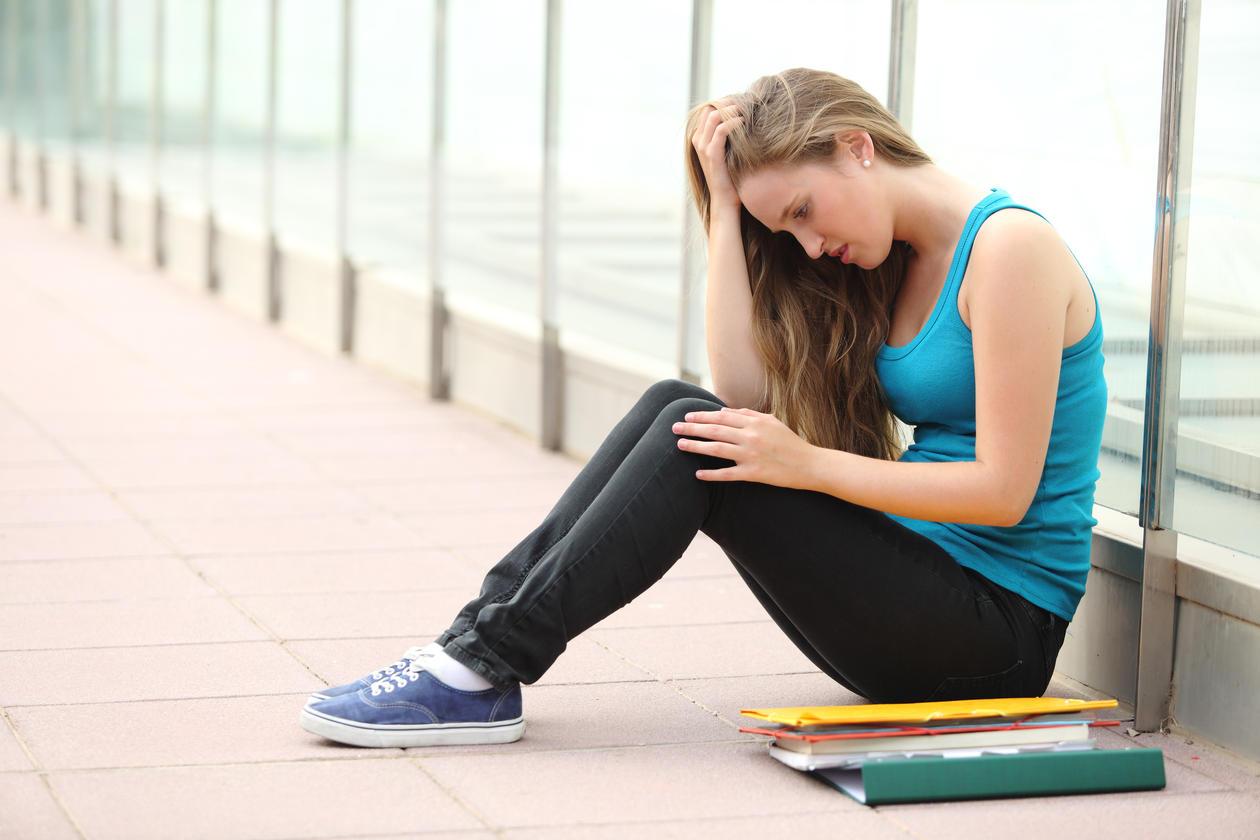 Illustrasjonsbilde Jente sitter på gulvet ved siden av skolebøker og ser fortvilet ut.