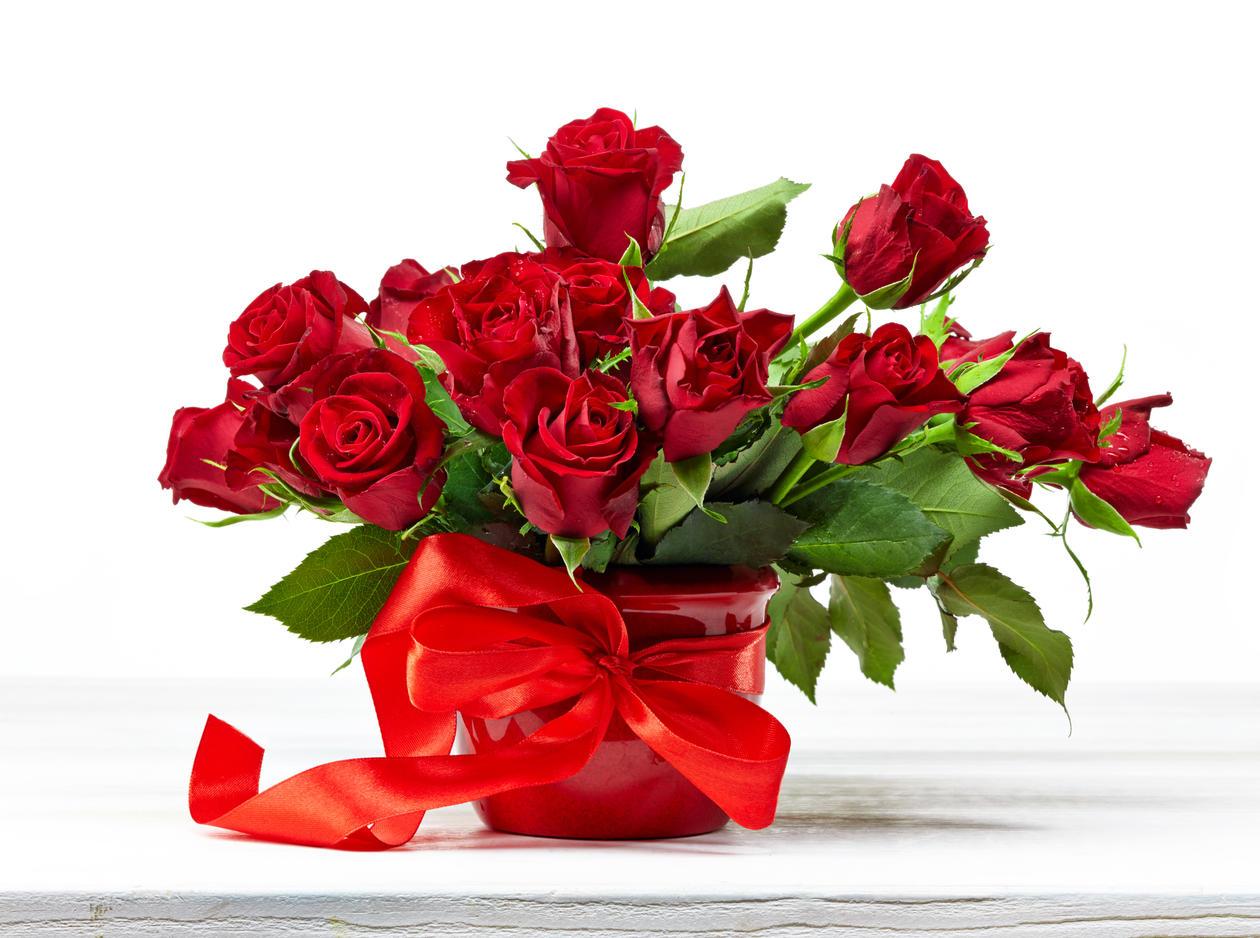Røde roser i vase med rød sløyfe