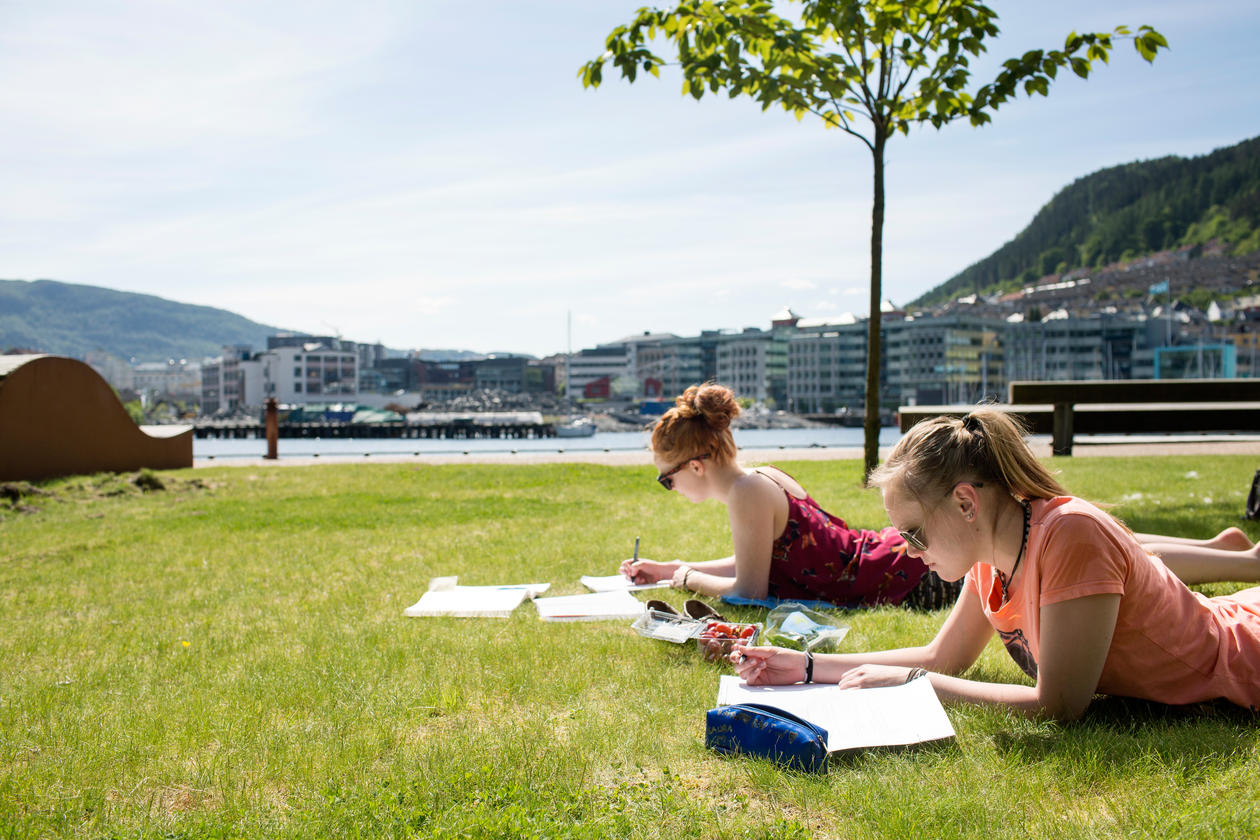 Two female students reading on the lawn outside with ocean view.