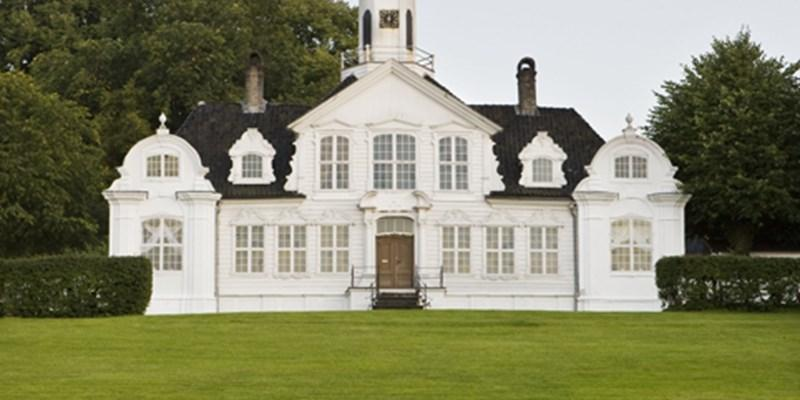 The old, wooden, whitepainted main building at Damsgaard hovedgård.