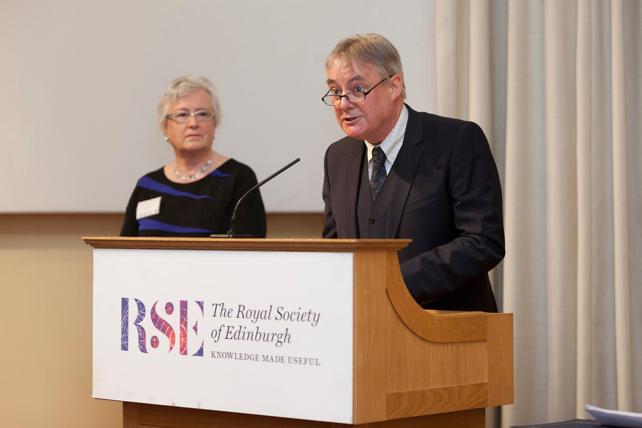 Hilary Birks (left) listening to Des Thompson (right) reading his citation about her