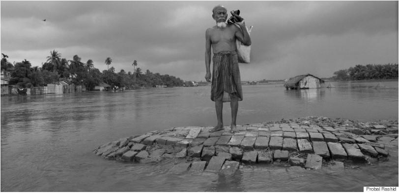 En eldre mann står i et oversvømmet område og ser utover