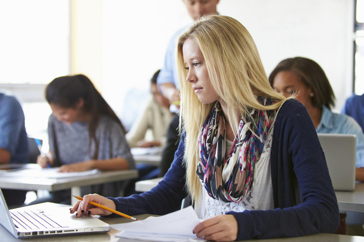 Ung kvinne som avlegger eksamen på laptop i klasserom