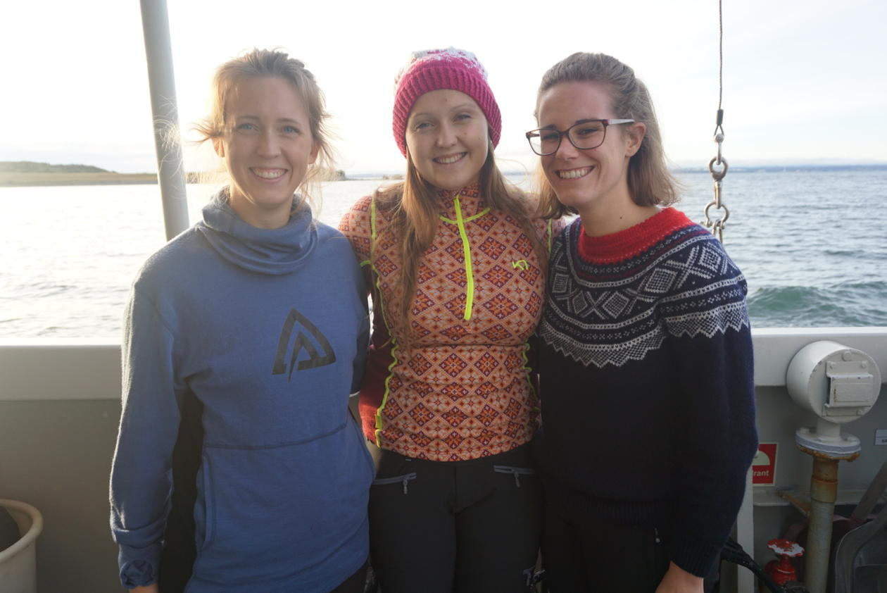 Smiling PhD students onboard the research vessel