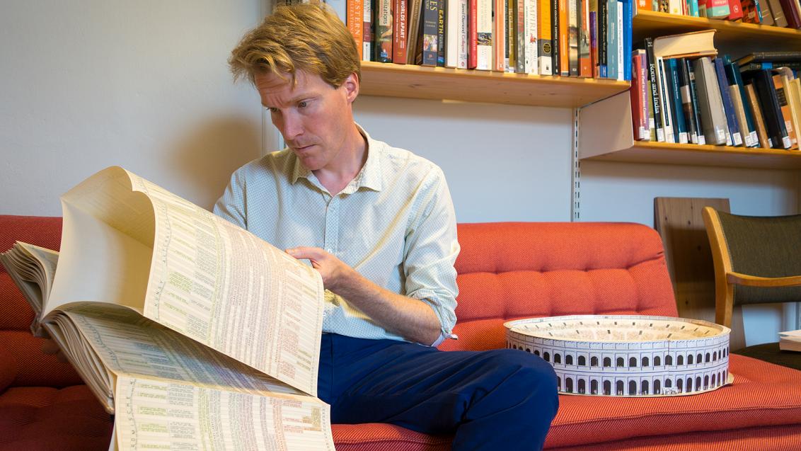Eivind Seland sit på ein sofa og blar i ei bok,
