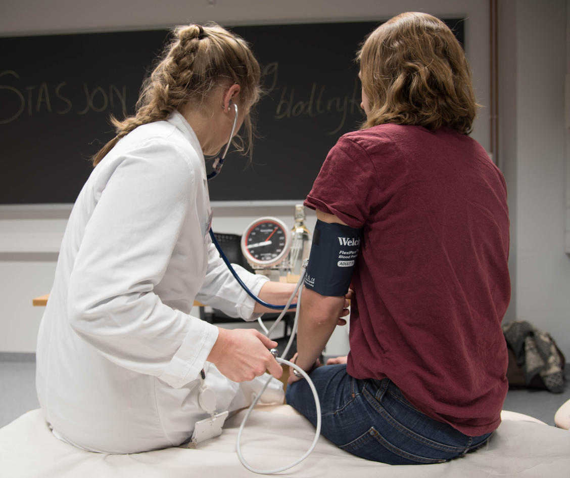 Medisinstudent sjekker blodtrykk på frivillig pasient
