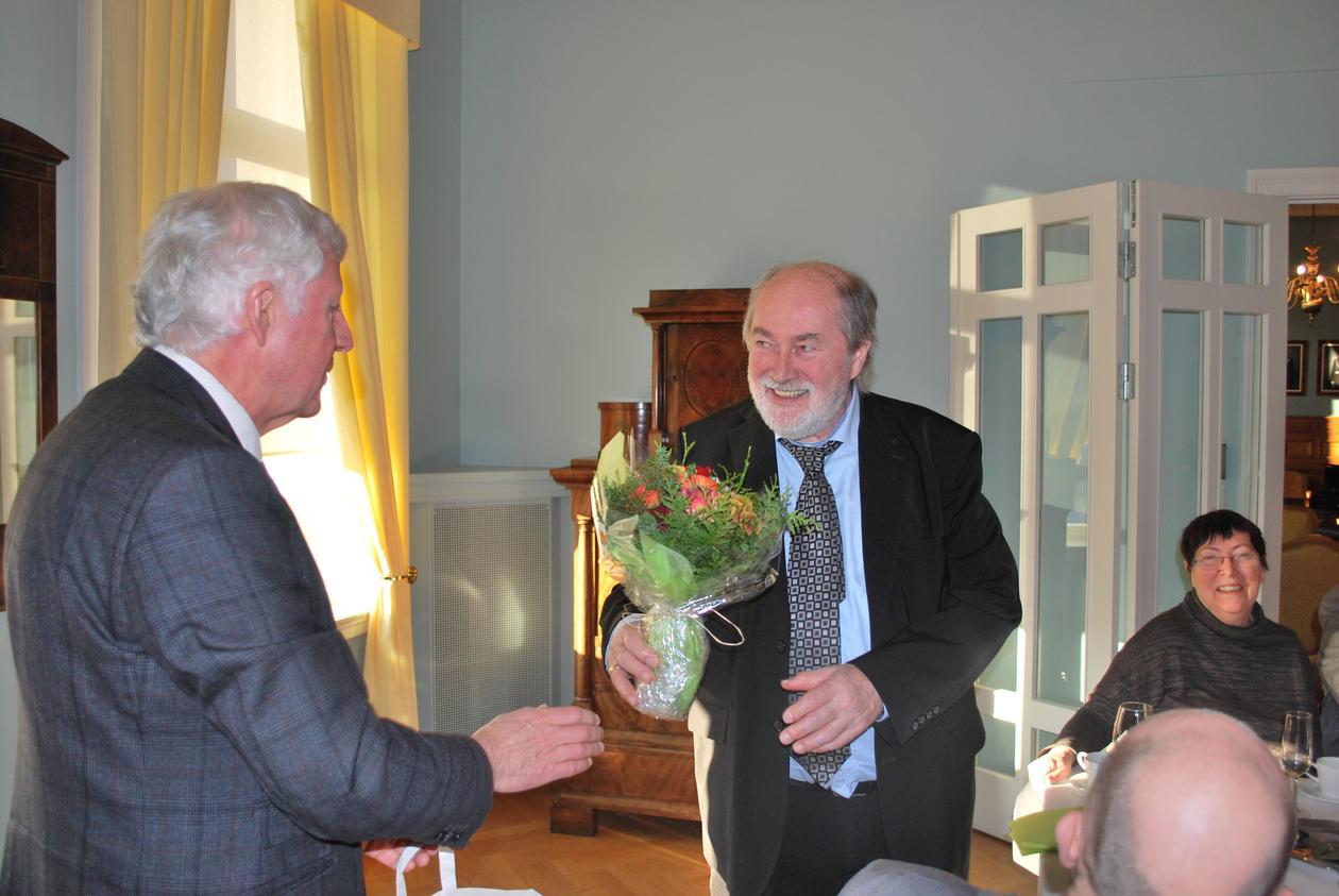 Prodekan ved HF, Einar Thomassen (t.v.), overrekker Anders Bjørkelo en bukett med blomster.