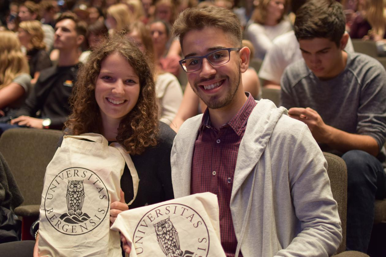 A male and a female student holding up UiB tote bags in front of a crowd