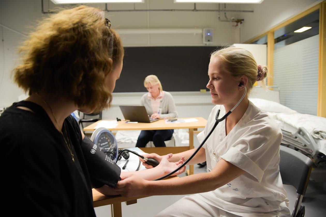 OSKE eksamen blodtrykkmåling av eksamenspasient. Eksaminator i bakgrunnen