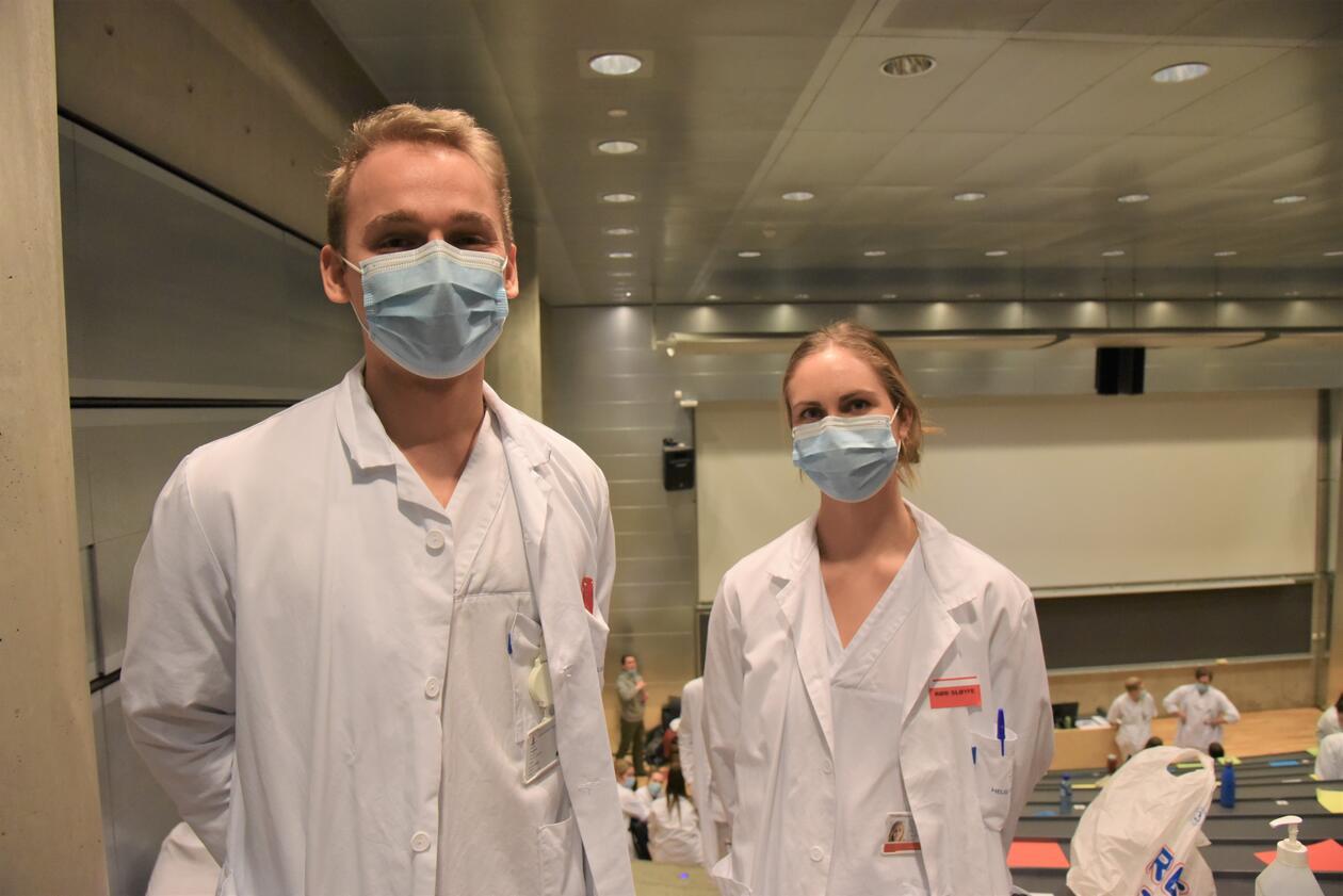 To studenter står med munnbind på i forelesningssalen. De har legefrakker på.