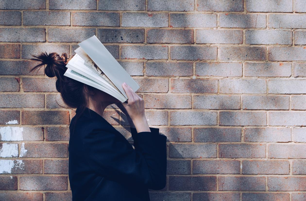 Student foran naturlig rustikk rød mursteinbakgrunn som holder bok opp foran ansiktet.