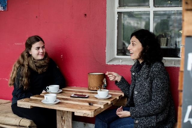Two female students drinking coffee at a café