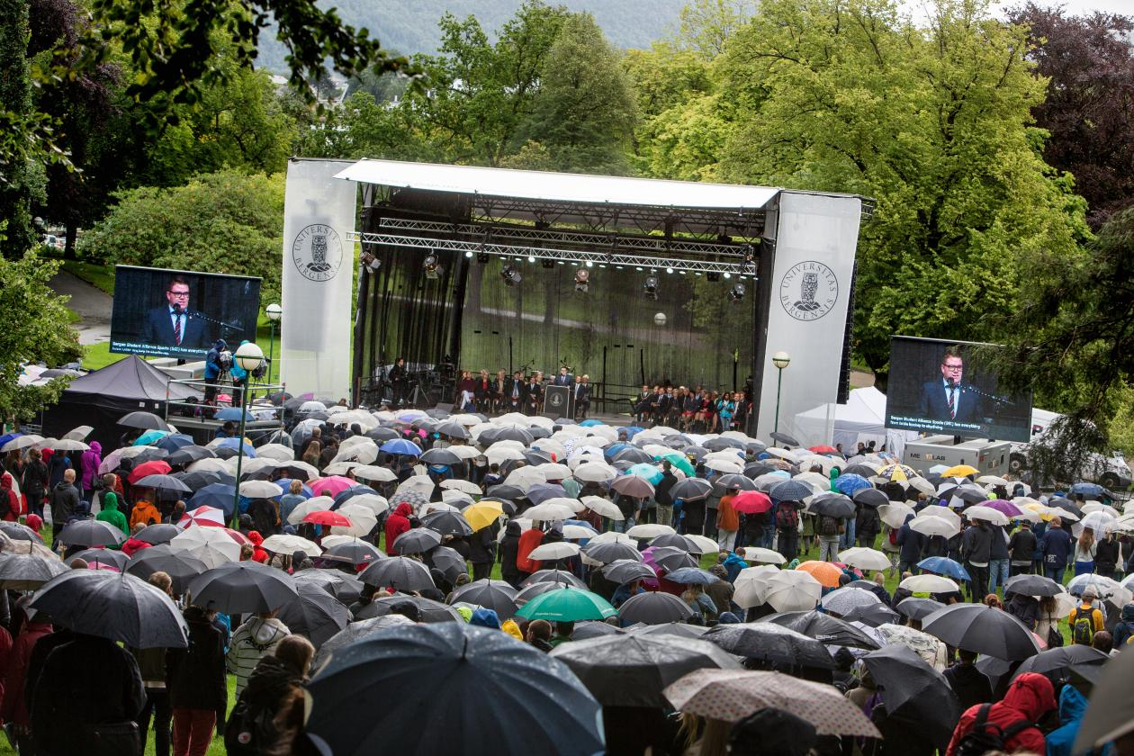Studenter med paraplyer foran scenen i Nygårdsparken