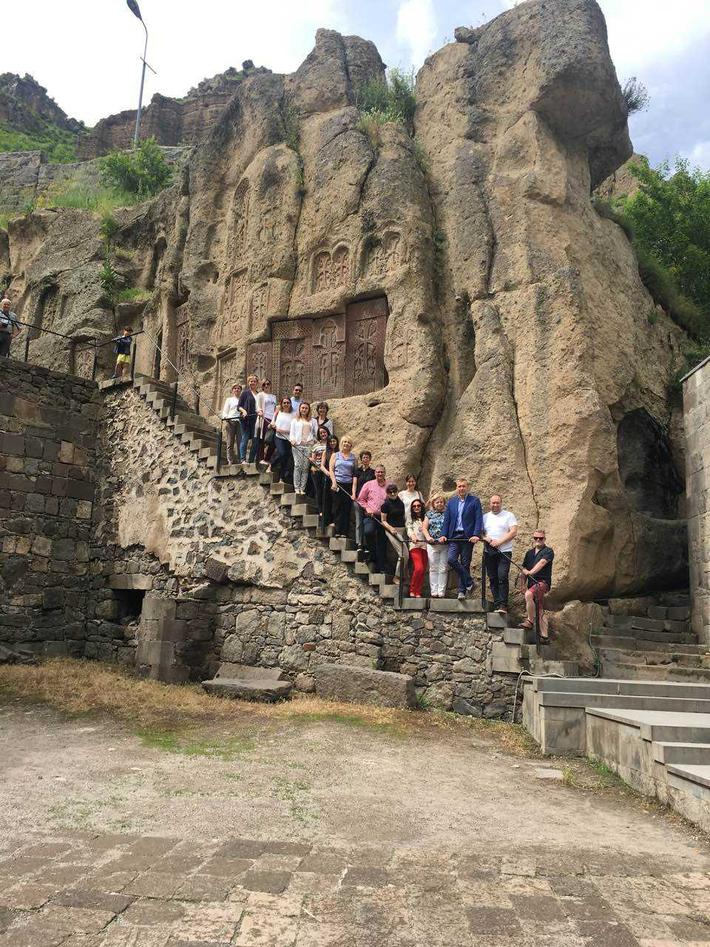 A group of people in front of a rock formation with ancient writing.