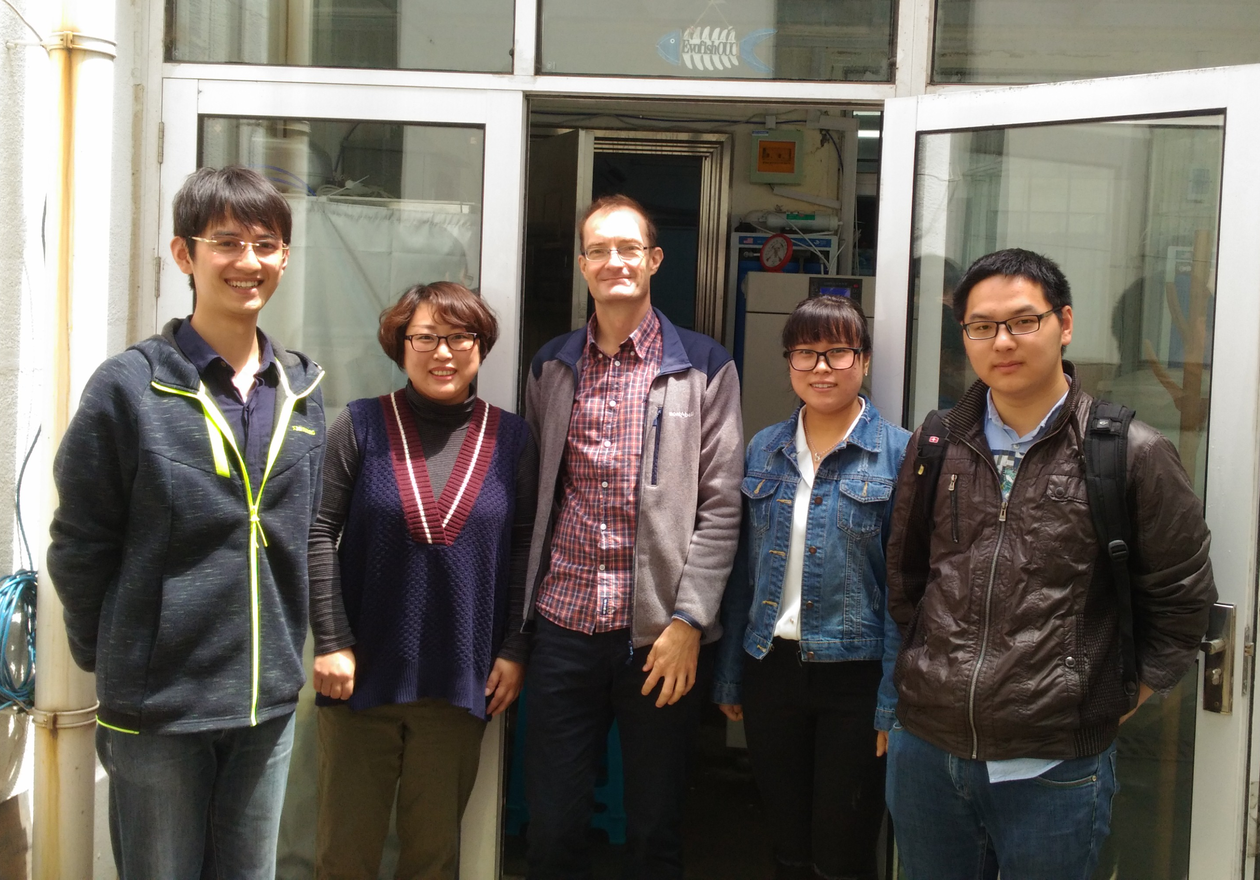 Group photo of five people in front of the laboratorium