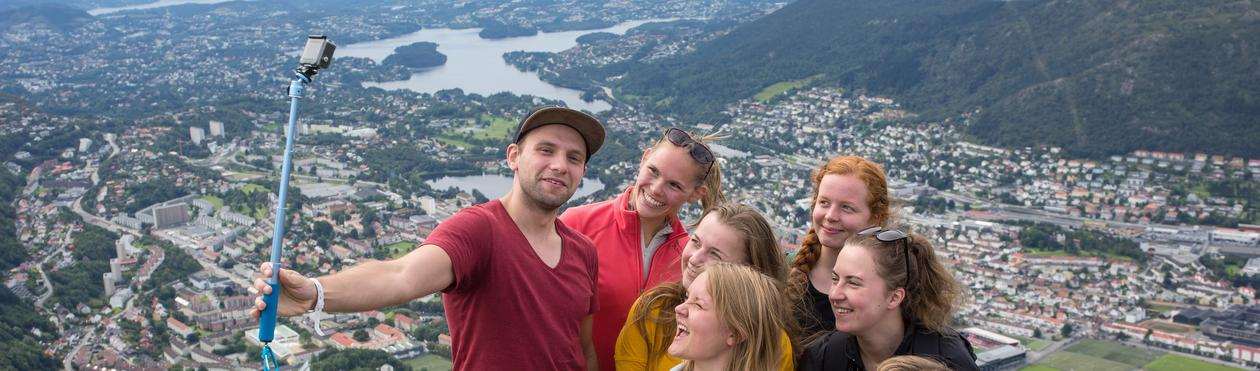 Students hiking taking a selfie with the city in the background