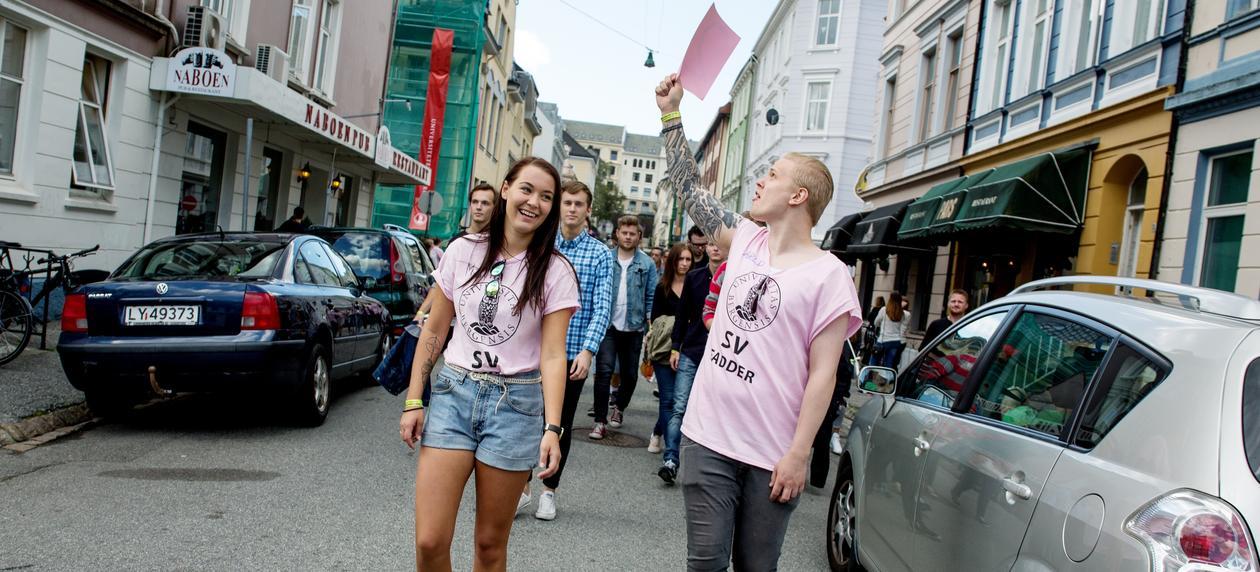 To fadderledere i rosa t-skjorter leder en gruppe fadderbarn gjennom en bergensgate.