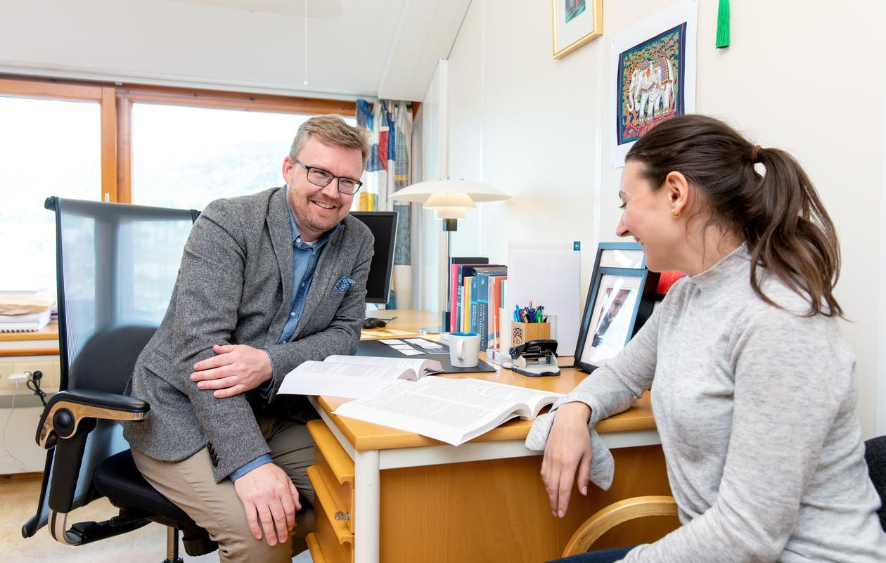 Student får veiledning av professor på kontor