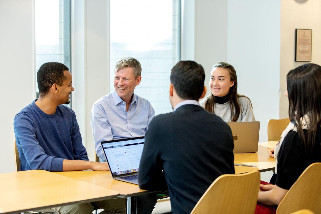 Bildet viser en ansatt i dialog med studenter