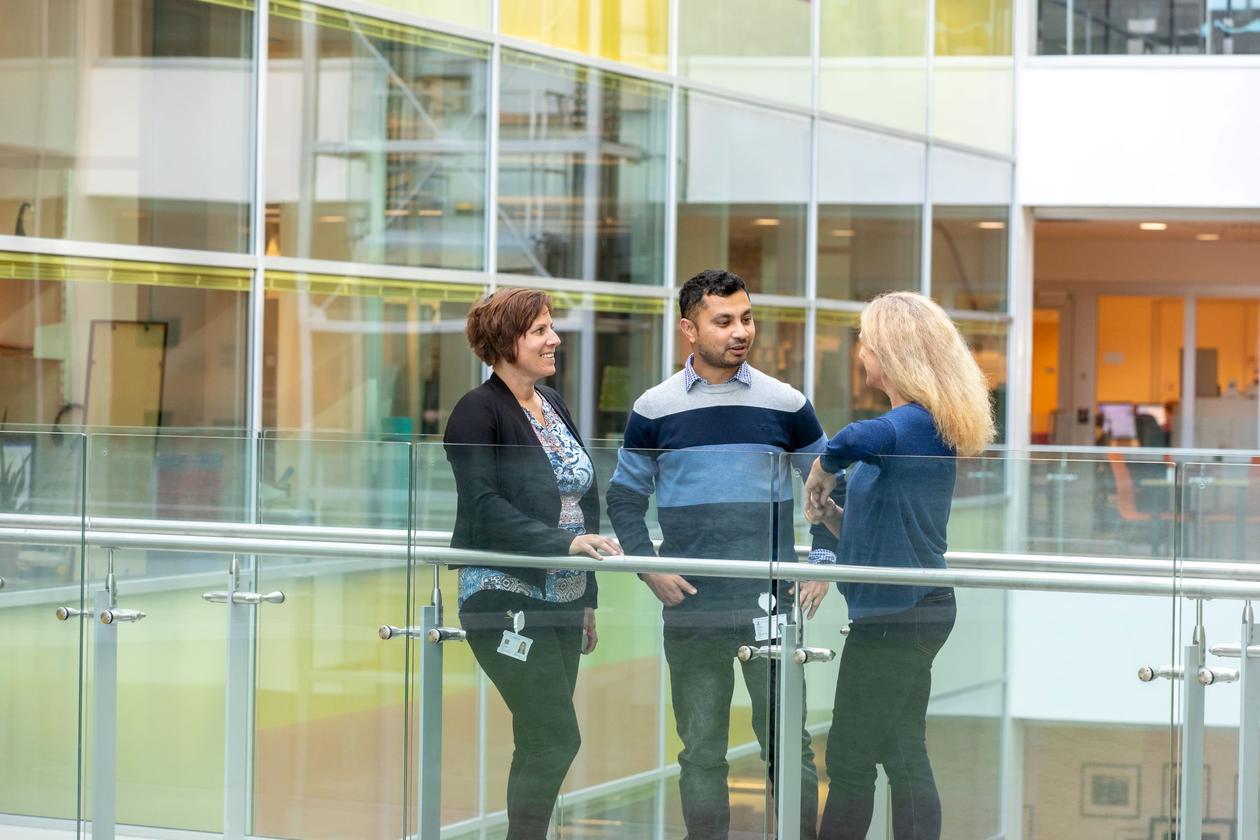 Bildet viser tre personer som snakker sammen.