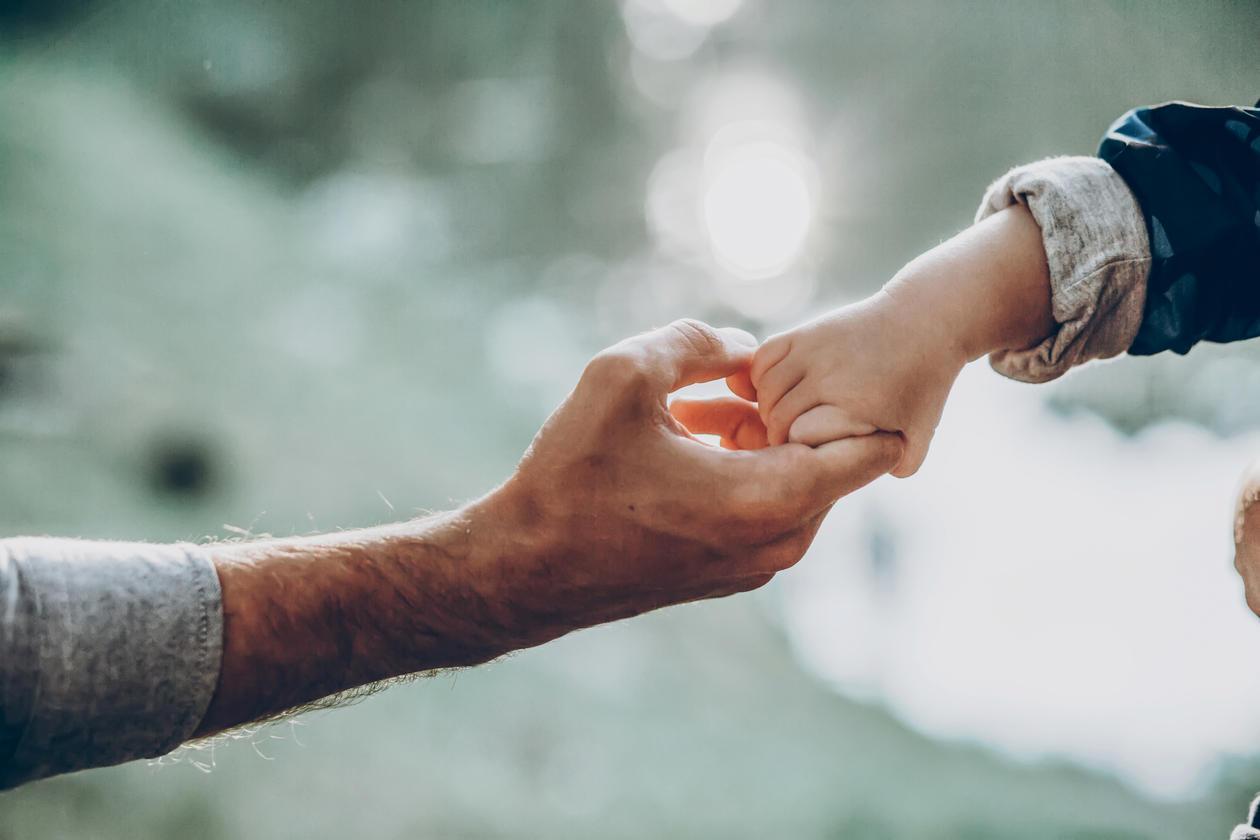 Foto av en mann som holder hender med en liten gutt