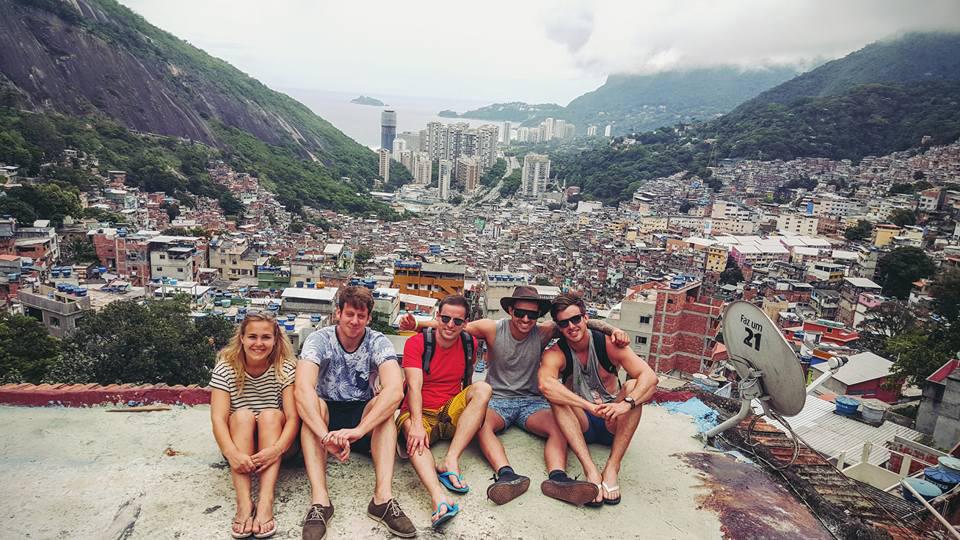 Gjeng studentar med slum-område i bakgrunnen