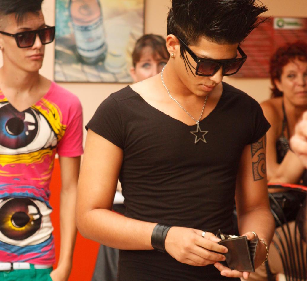 Gutt taster på sin mobil før konsert i Havana, Cuba. Den punkete sveisen er en kopi av frisyren til artistene som skal til å opptre.
