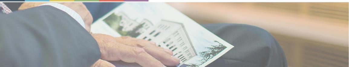 hånd som holder et dokument med museumsbygningen avbildet