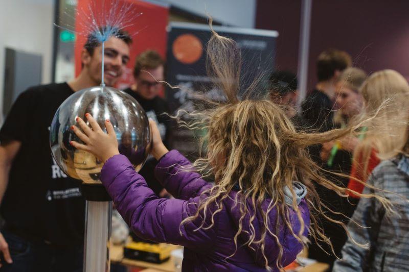 Et barn gjør fysikkeksperiment, holder på en elektrisk kule og håret reiser seg